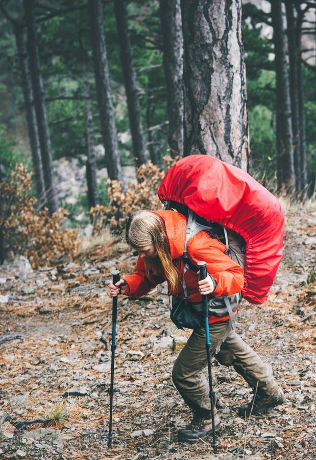 有远足在狂放的森林里的大背包的妇女旅客 免版税图库摄影