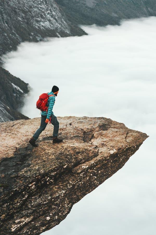 有远足在Trolltunga岩石峭壁的背包的人 库存图片