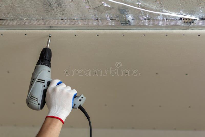 有连接暂停的干式墙天花板的螺丝刀的工作者手金属化框架 整修、建筑和DIY概念 免版税库存照片