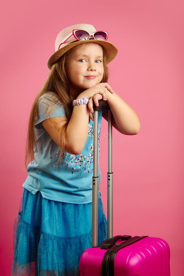 有迷人的微笑的美丽的女孩,穿戴在草帽和太阳镜,看照相机,拿着电话 库存照片