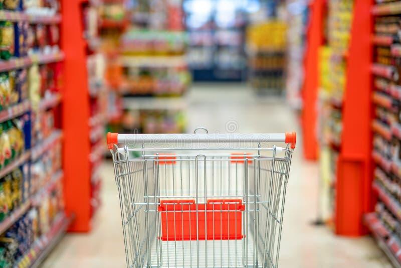 有迷离超级市场商店走道和产品架子内部背景的空的手推车 库存图片