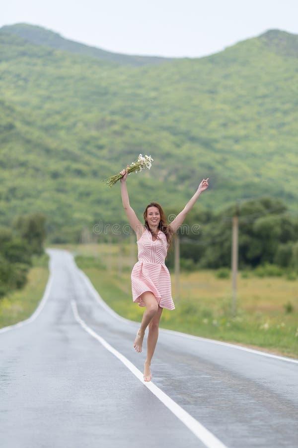 有追捕沿路的春黄菊花束的赤足女孩镭 免版税库存图片