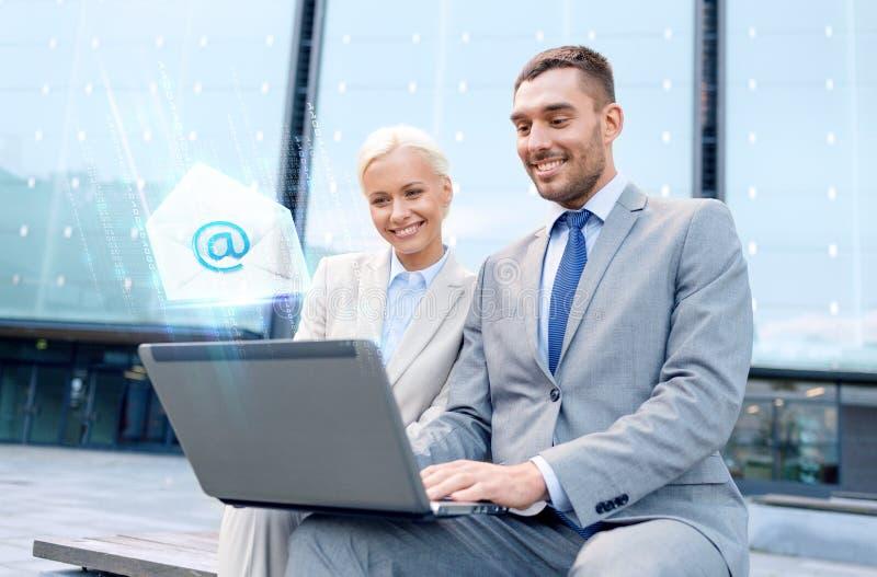 有送电子邮件的膝上型计算机的微笑的买卖人 免版税库存照片