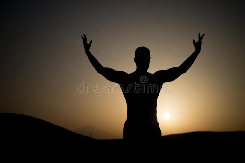 有适合剪影的人在日落天空 运动员用在自然风景的被举的手 运动员展示力量 在夏天黄昏的锻炼 免版税库存照片