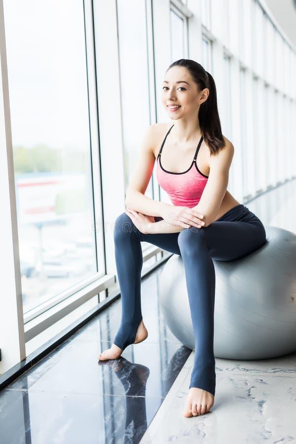 有适合球的美丽的女孩 解决与pilates球,放松和休息在锻炼以后的健身妇女 免版税图库摄影