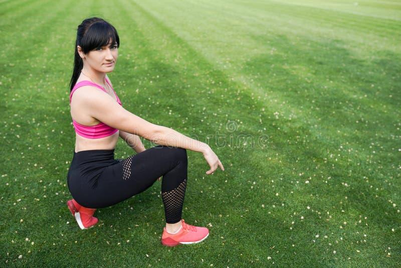 有适合的身体的女孩在与拷贝空间的绿色背景 在行使的运动服的女性模型户外 免版税库存图片