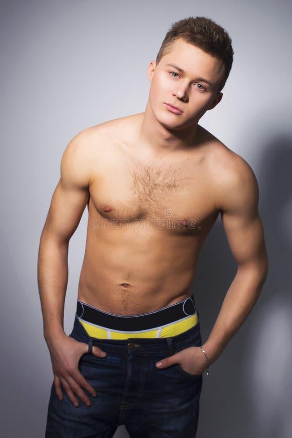 有适合身体倾斜的赤裸上身的英俊的人对墙壁 库存照片