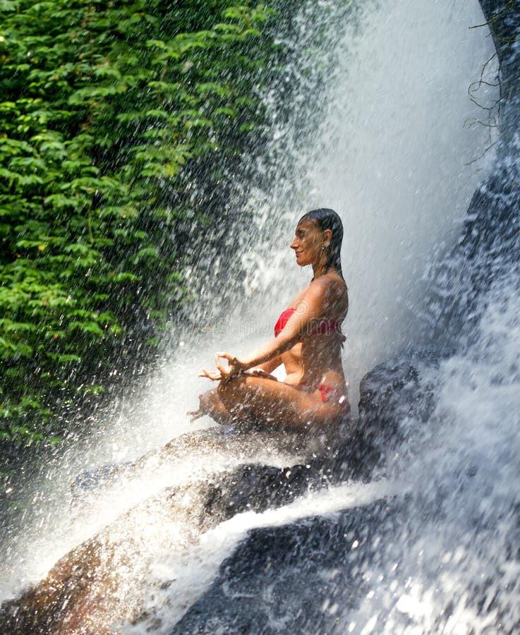 有适合身体实践的瑜伽湿下面热带天堂瀑布小河的年轻可爱和愉快的30s妇女在凝思和 库存图片