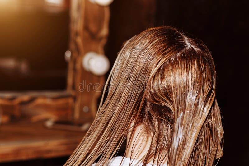 有适用于面具的刷子的发式专家她的秀丽美发店的客户的头发 调直角质素的过程,头发 免版税图库摄影