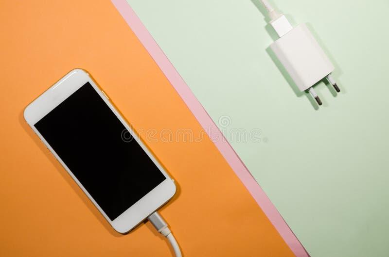 有适配器块的一个充电的电话 免版税库存照片