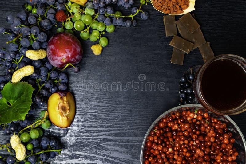 有逆转醇、葡萄、李子、goji、花生、蔓越桔、raspberrys、黑暗的巧克力、红葡萄酒或者石榴汁的食物富有 免版税库存图片