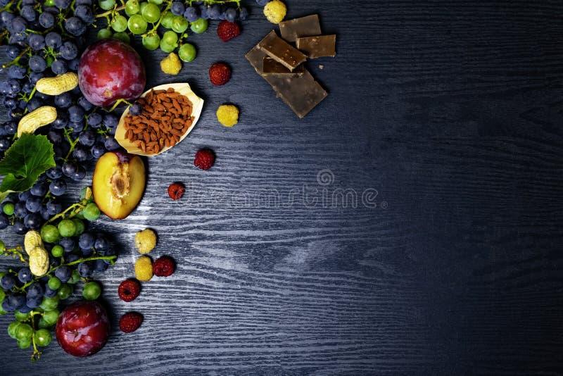 有逆转醇的食物富有,葡萄,李子, goji,花生,蔓越桔,在黑木背景的raspberrys巧克力 库存图片