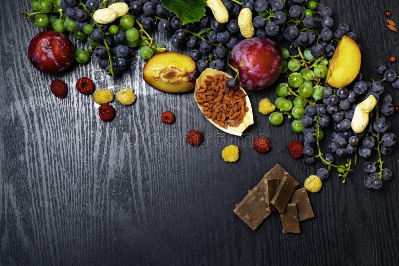 有逆转醇的食物富有,葡萄,李子, goji,花生,蔓越桔,在黑木背景的raspberrys巧克力 免版税库存图片