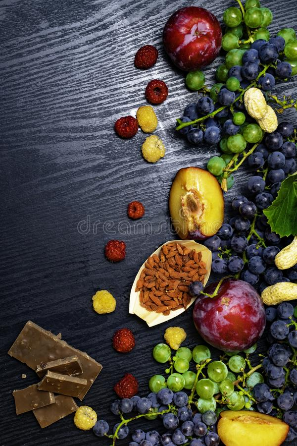 有逆转醇的食物富有,葡萄,李子, goji,花生,蔓越桔,在黑木背景的raspberrys巧克力 免版税库存照片