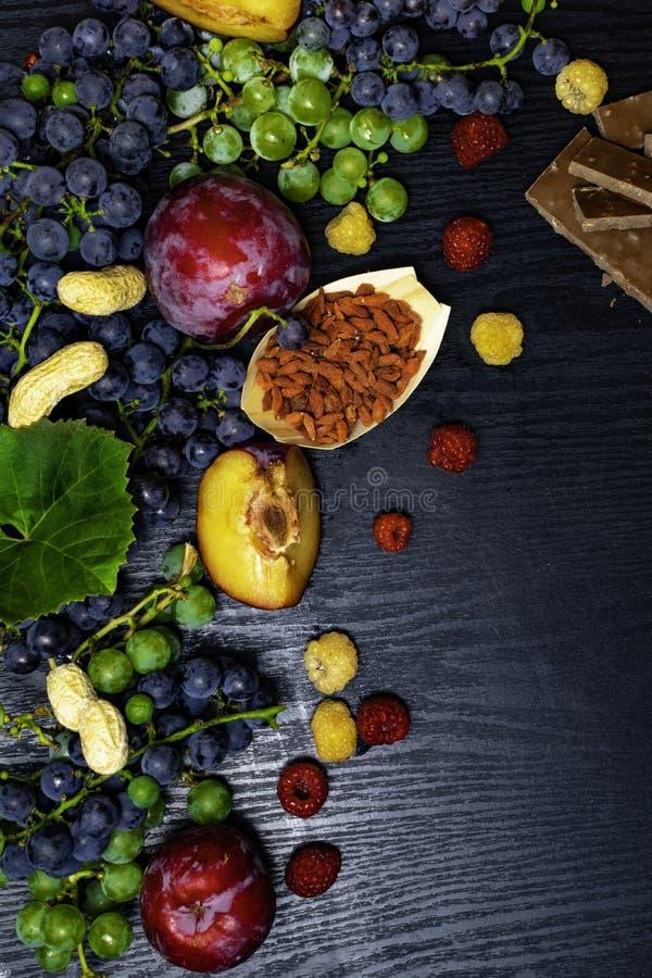 有逆转醇的食物富有,葡萄,李子, goji,花生,蔓越桔,在黑木背景的raspberrys巧克力 库存照片