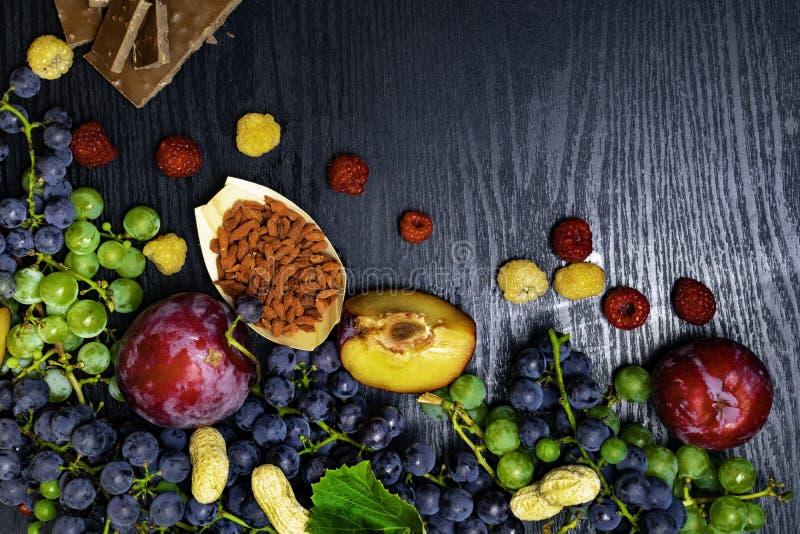 有逆转醇的食物富有,葡萄,李子, goji,花生,蔓越桔,在黑木背景的raspberrys巧克力 免版税图库摄影