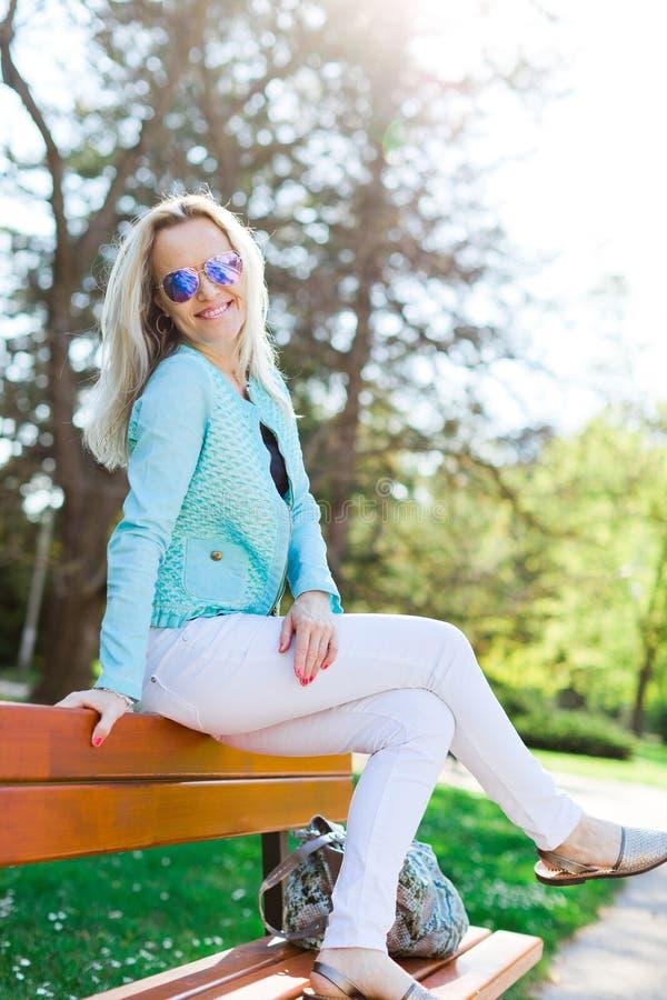 有选址在长凳的太阳镜的白肤金发的可爱的妇女 免版税库存图片