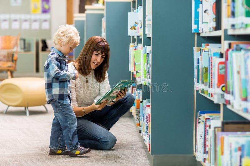 有选择书的老师的男孩从书架 免版税库存照片