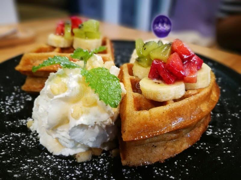 有选择性集中于与滑的草莓和香蕉顶部的奶蛋烘饼服务与在黑色的盘子的纯奶油 免版税库存图片