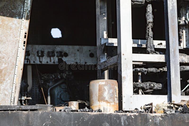 有透气的损坏的超级市场锅炉室,涡轮,在与烧伤黑色黑暗的残骸强烈的灼烧的火的放火火以后 图库摄影