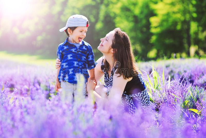 有逗人喜爱的儿子的愉快的妈妈淡紫色背景的 美丽的妇女 库存图片