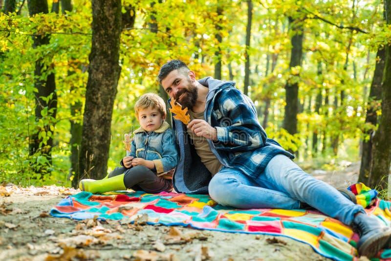 ?? 有逗人喜爱的儿子的行家有胡子的爸爸一起花费时间在森林家庭时间 r o 免版税库存图片