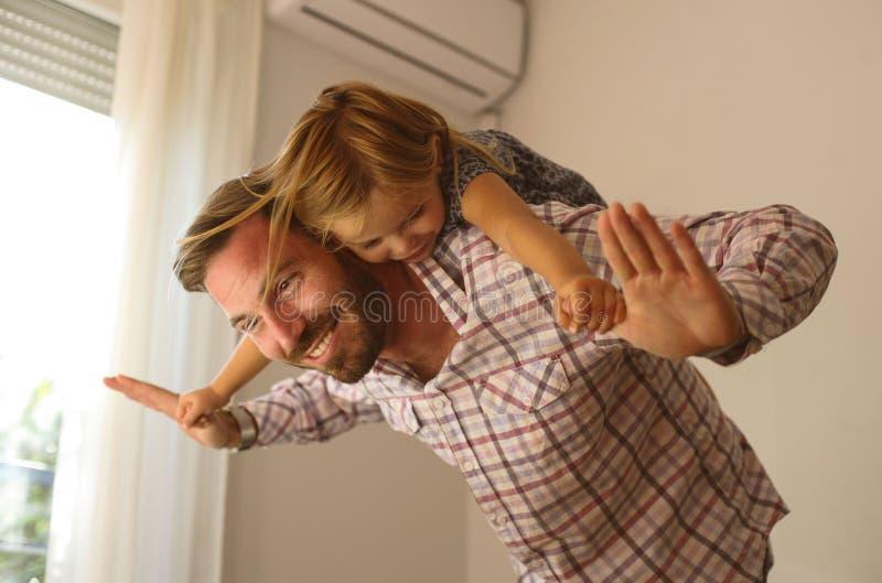 有逗人喜爱的女儿的年轻爸爸在家 库存图片