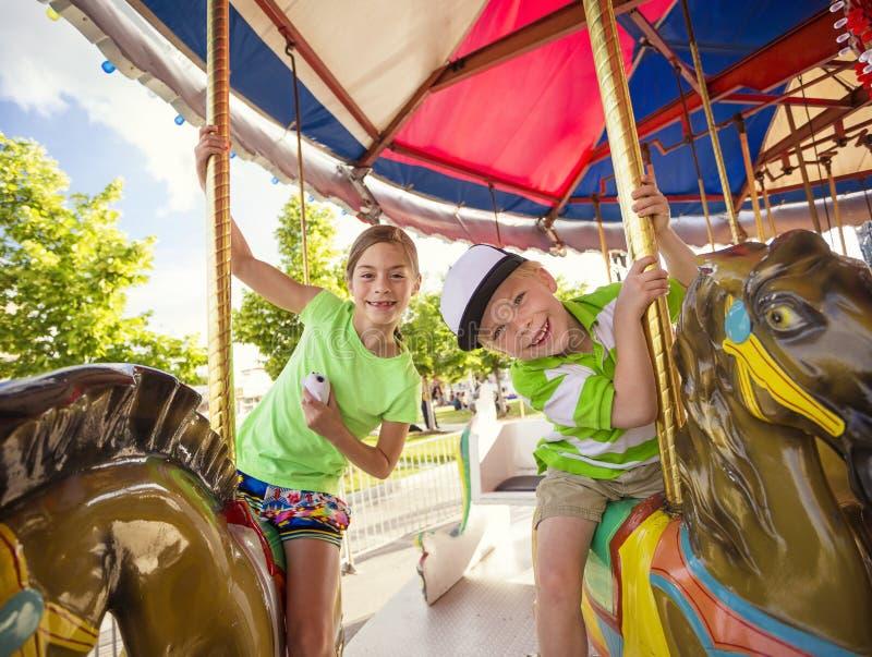 有逗人喜爱的孩子在一个五颜六色的狂欢节转盘的乐趣骑马 免版税库存照片