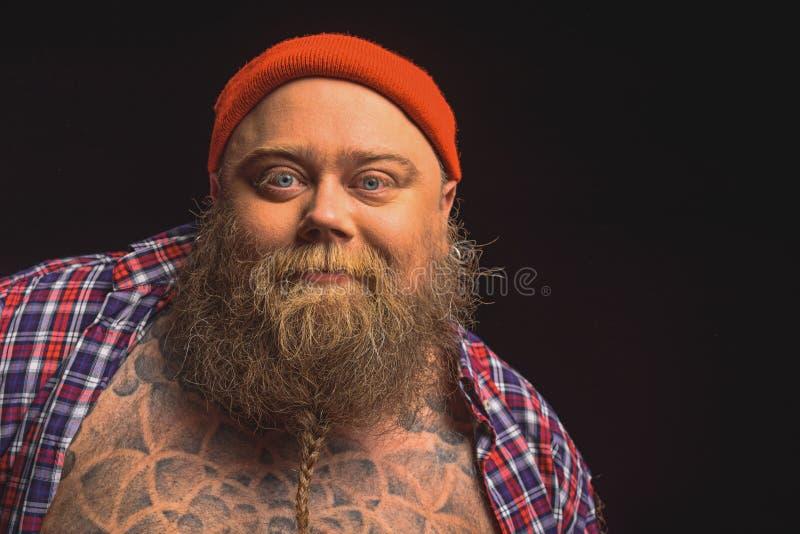 有逗人喜爱的微笑的愉快的肥胖男性行家 免版税库存图片