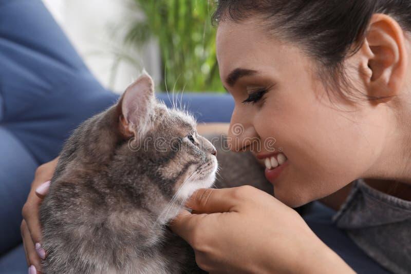 有逗人喜爱的猫的年轻女人在家 免版税库存图片