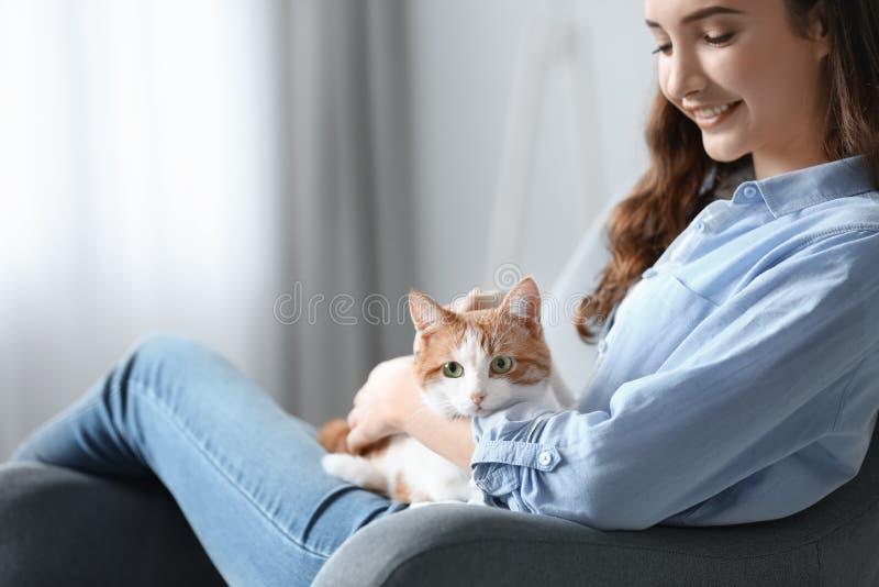 有逗人喜爱的猫的美丽的少妇在扶手椅子 免版税库存照片