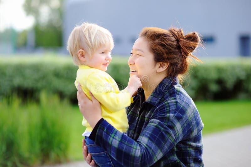 有逗人喜爱的白种人小孩男孩的年轻亚裔妇女 库存图片