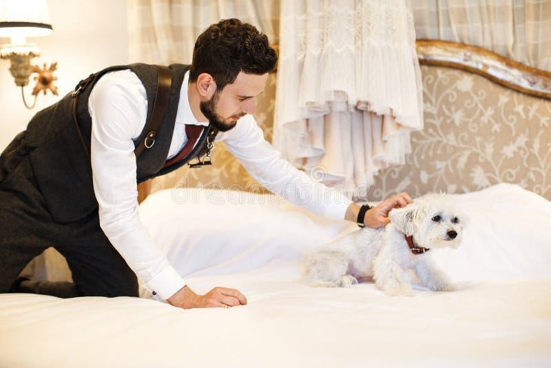 有逗人喜爱的白色狗的人 垂悬在床上的婚礼礼服在屋子里 图库摄影