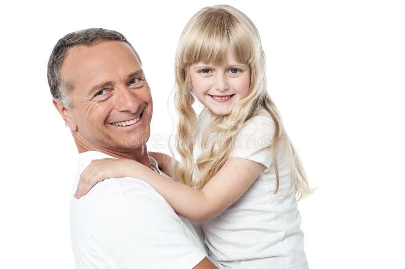 有逗人喜爱的矮小的女儿的快乐的父亲 免版税库存图片