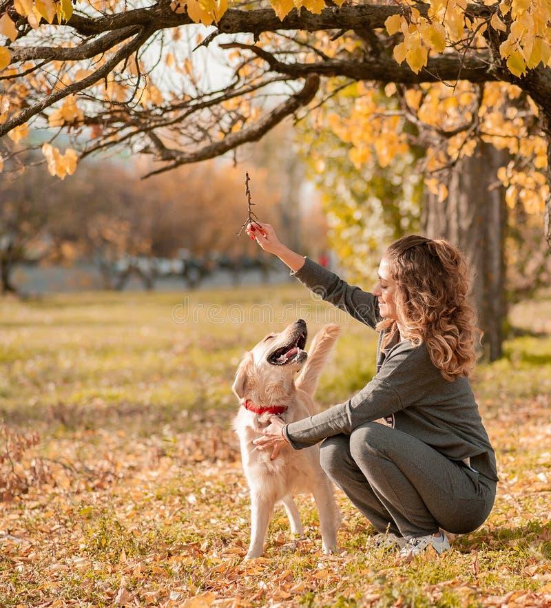 有逗人喜爱的金毛猎犬狗的美丽的微笑的妇女 免版税库存图片