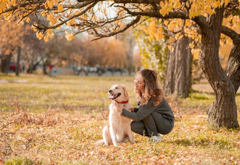 有逗人喜爱的金毛猎犬狗的美丽的微笑的妇女 库存照片