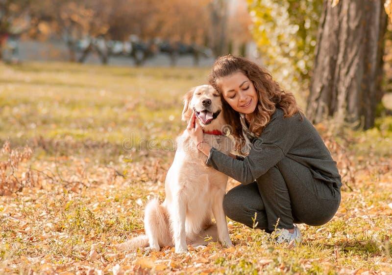 有逗人喜爱的金毛猎犬狗的美丽的微笑的妇女 库存图片