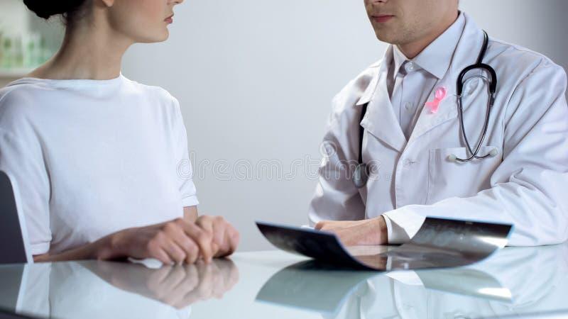 有通知关于乳房X线照片结果的桃红色丝带的癌症医师女性患者 库存图片