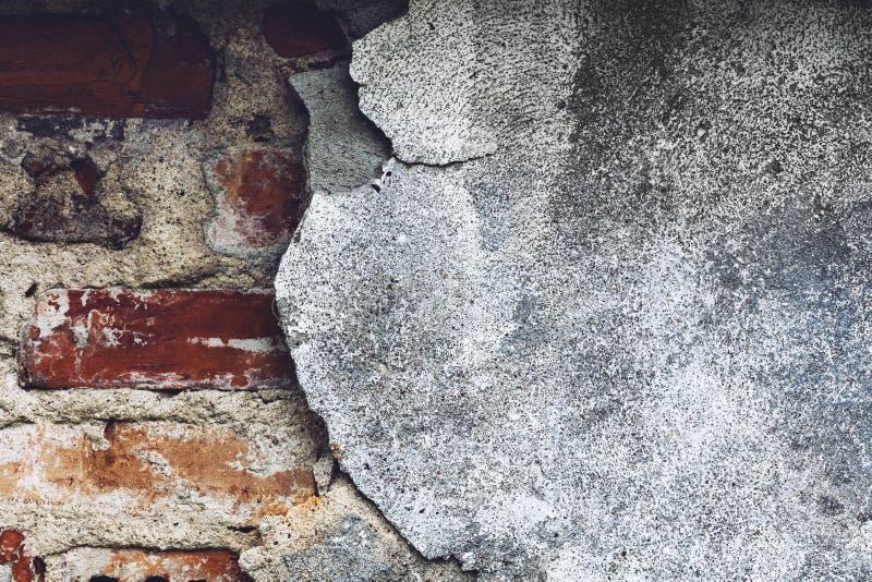 有通过偷看的红砖的损坏的灰色墙壁 图库摄影