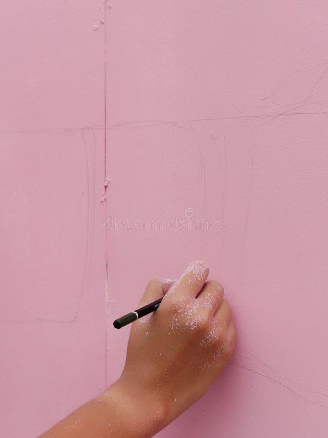 有速写书刊上的图片的铅笔的一只艺术家手在桃红色墙壁 免版税图库摄影