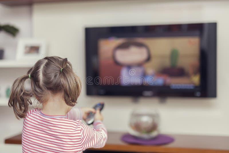 有遥控的小逗人喜爱的女孩更换在电视的渠道 免版税图库摄影
