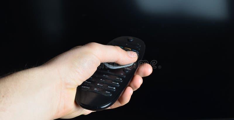有遥控的电视的一只男性手打开在黑屏幕背景的电视 库存照片