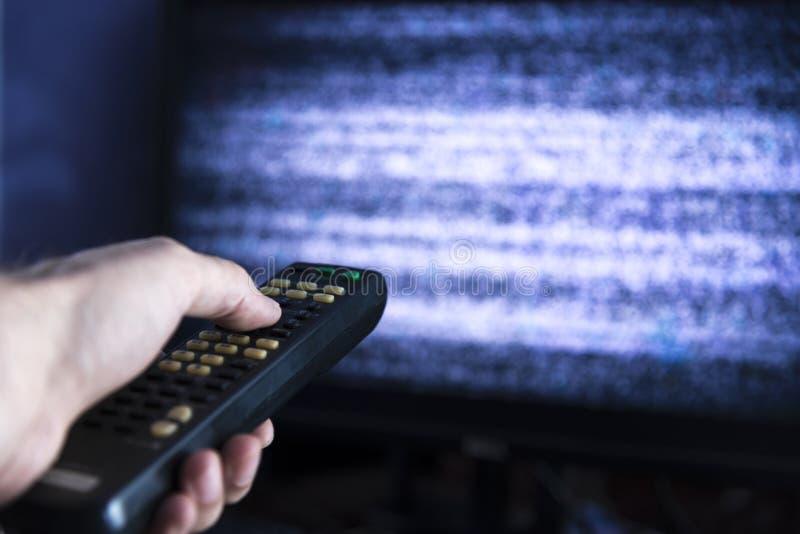 有遥控的男性手从电视 免版税图库摄影