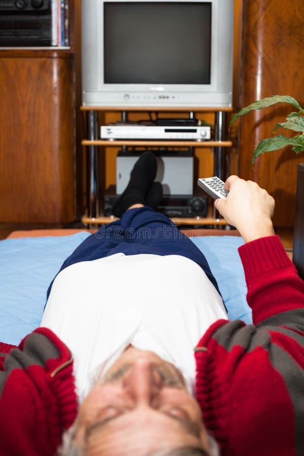 有遥控观看的电视的年长人 免版税库存照片