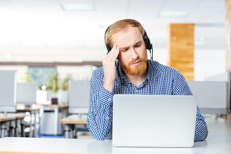 有遭受在工作场所的头疼的耳机和膝上型计算机的人 免版税库存照片