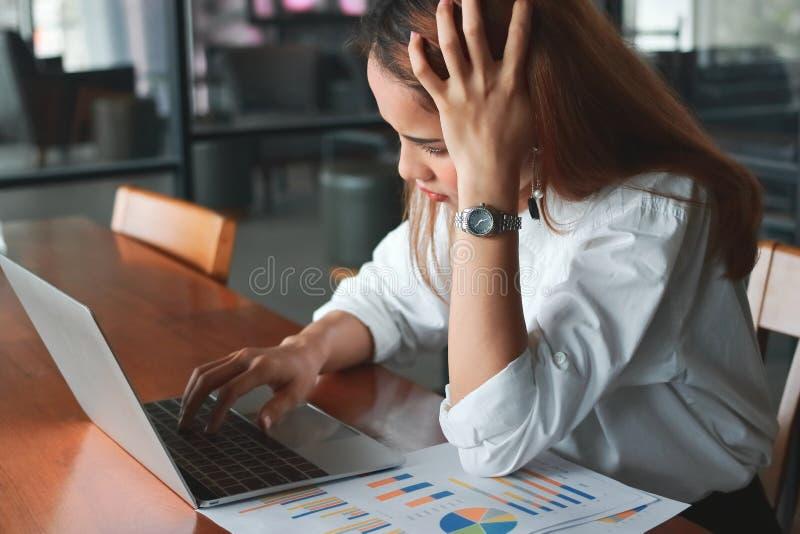 有遭受紧张的膝上型计算机的沮丧的沮丧的年轻亚裔女商人在办公室 免版税库存图片