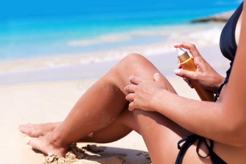 有遮光剂奶油的年轻人相当亭亭玉立的白肤金发的妇女在海滩 免版税库存照片