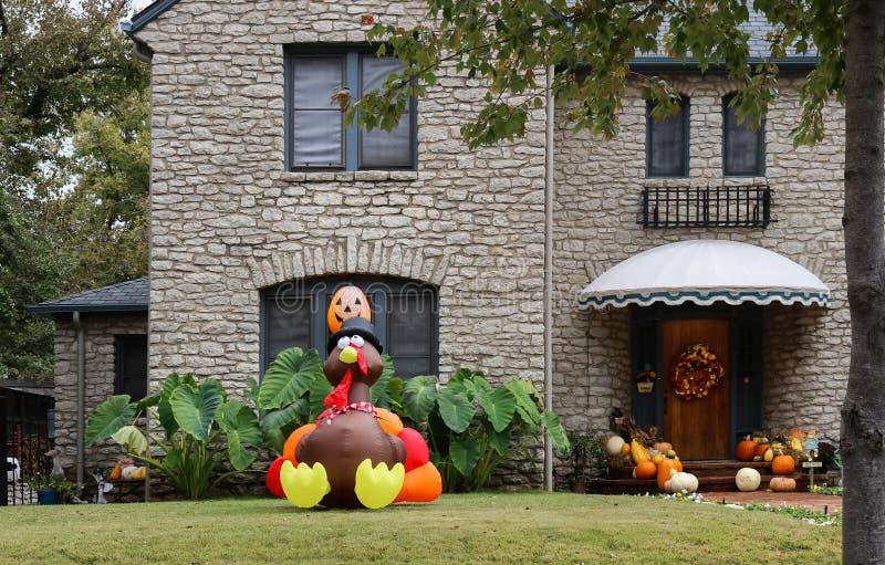 有遮篷的俏丽的石房子和秋天在门和许多南瓜缠绕在门廊和大爆炸火鸡在环境美化的前院 免版税库存图片