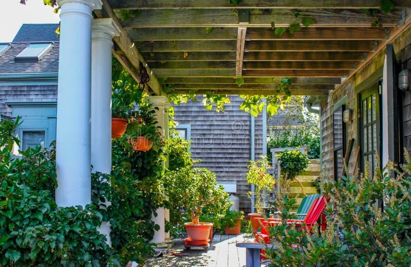 有遮荫门廊的墙板房子与有生长在大量和五颜六色的adirondack的葡萄树和其他植物的荫径屋顶 库存图片