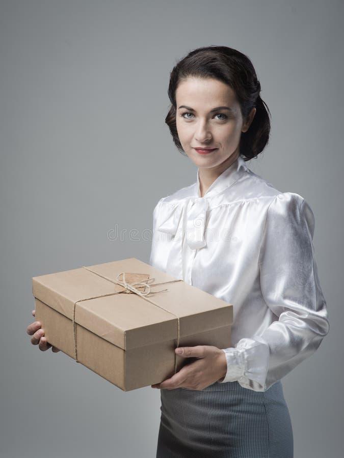 有邮件包裹的微笑的葡萄酒妇女 库存照片